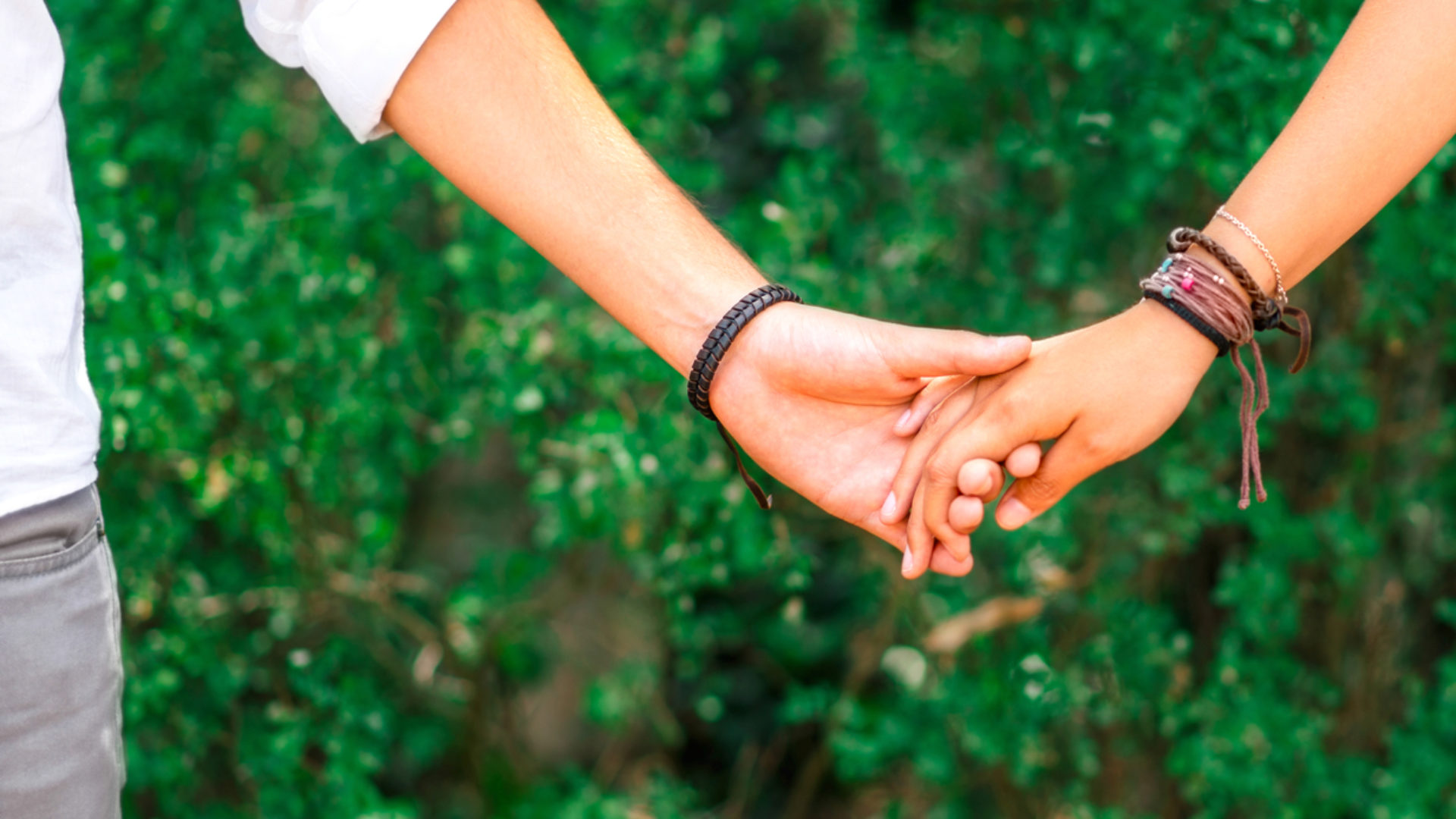 couple holding hands in a garden