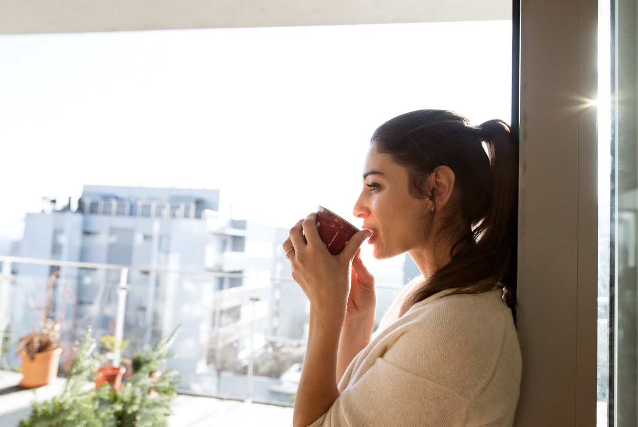 Woman drinking coffee and thinking about gratitude
